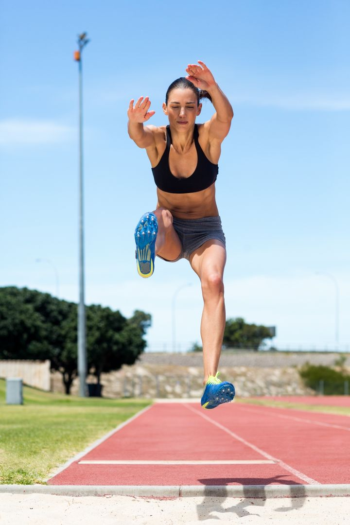 Female athlete performing a long jump during a competition Free Stock Images from PikWizard