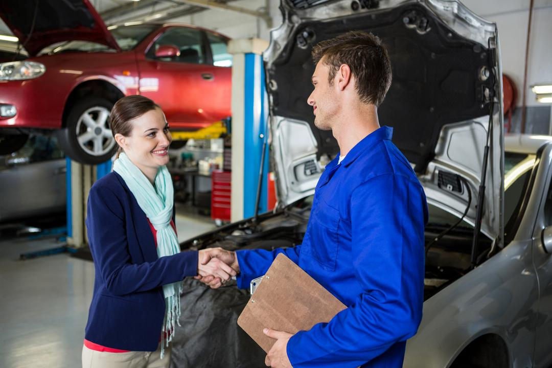 Satisfied customer shaking hands with mechanic at repair garage