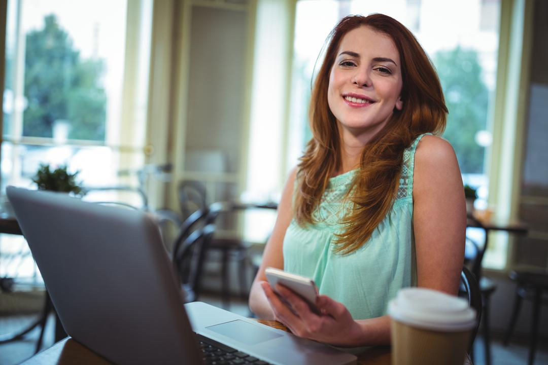 Portrait of woman using laptop and mobile phone in café