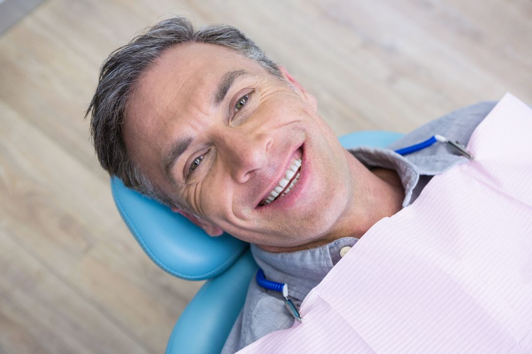 Overhead portrait of smiling man sitting on chair at dentist clinic Free Stock Images from PikWizard