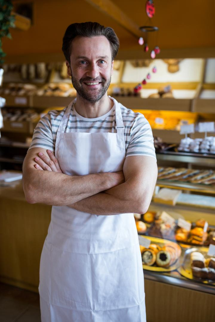 Portrait of smiling owner standing in bakery shop with his hands crossed