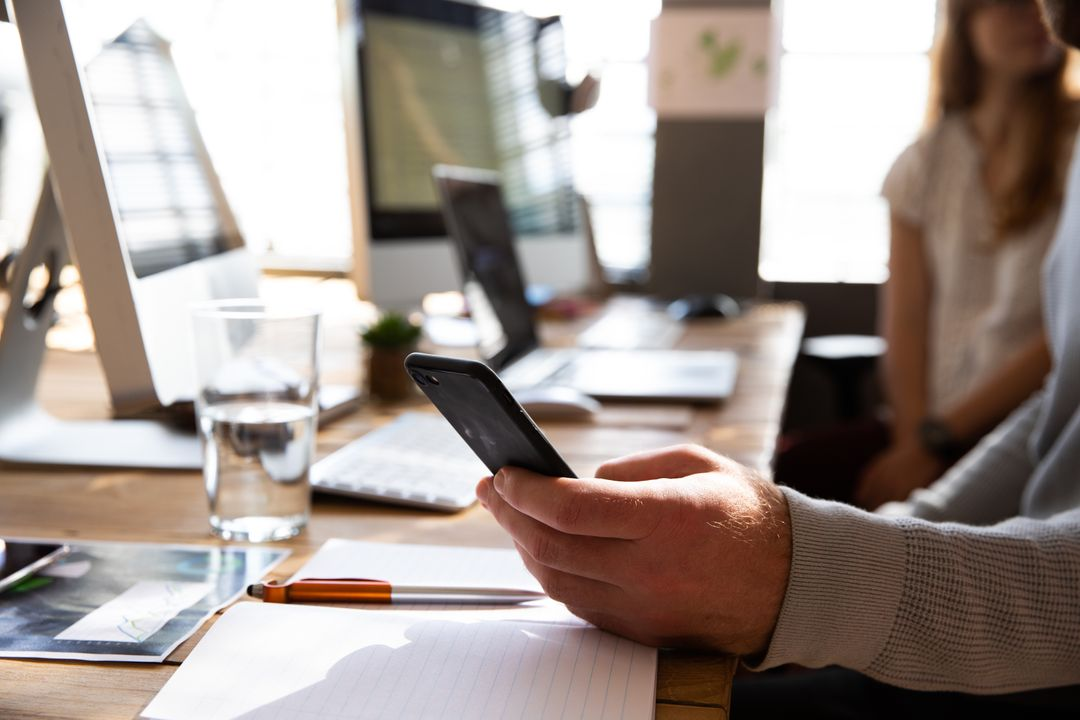 Close up image of a business worker on their phone at a shared desk