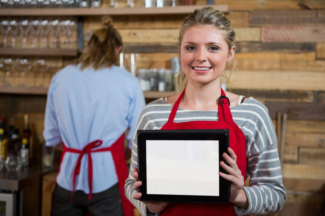 Portrait of smiling young woman showing digital tablet with male colleague in background at coffee shop