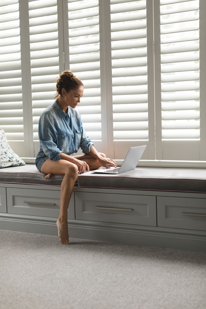 Beautiful woman using laptop while sitting on window seat in a comfortable home Free Stock Images from PikWizard