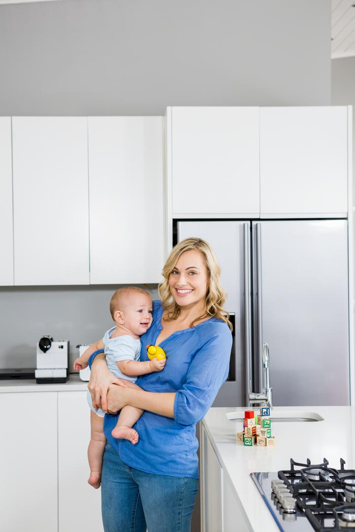 Mother holding her baby boy in kitchen at home