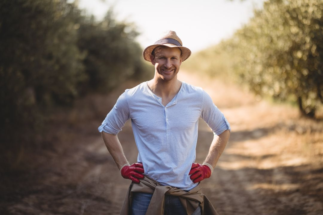 Portrait of smiling young man standing on dirt road at farm