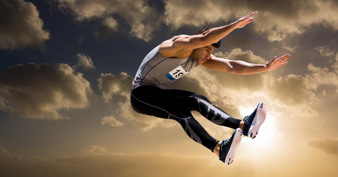Athlete jumping in air against cloudy sky