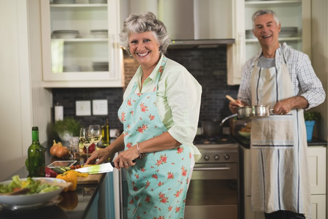 Portrait of smiling senior couple cooking in kitchen at h