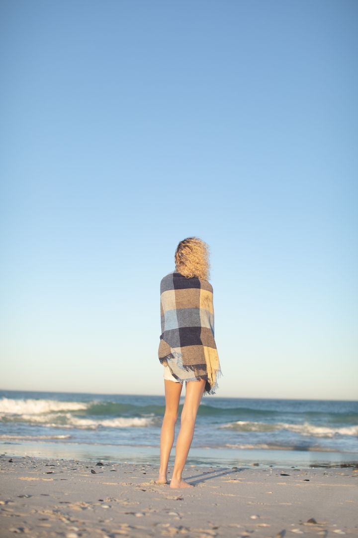 Rear view of woman wrapped in blanket standing on the beach