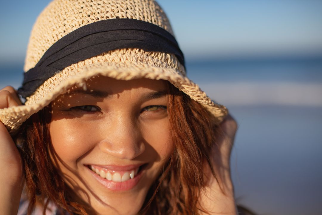 Close-up of beautiful mixed race woman with hat looking at camera on beach in the sunshine