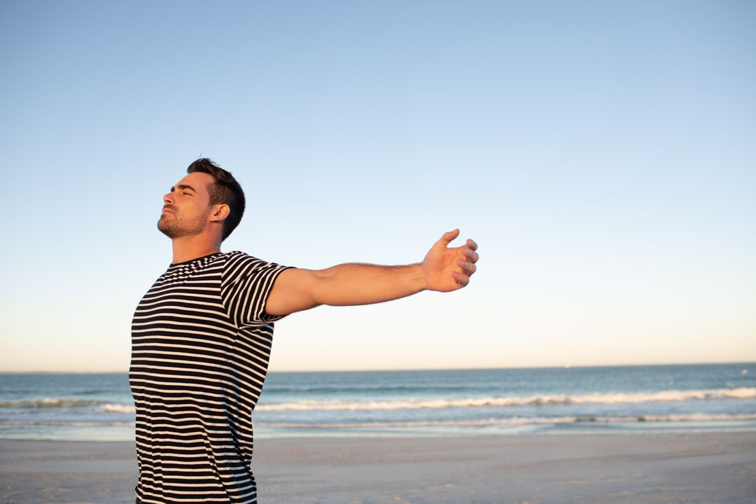 Side view of man standing with arms outstretched on the beach