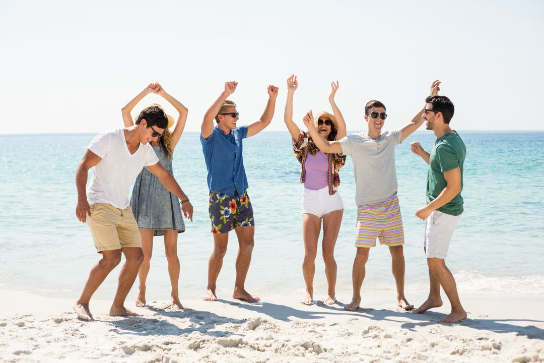 Full length of young friends dancing at beach on sunny day Free Stock Images from PikWizard