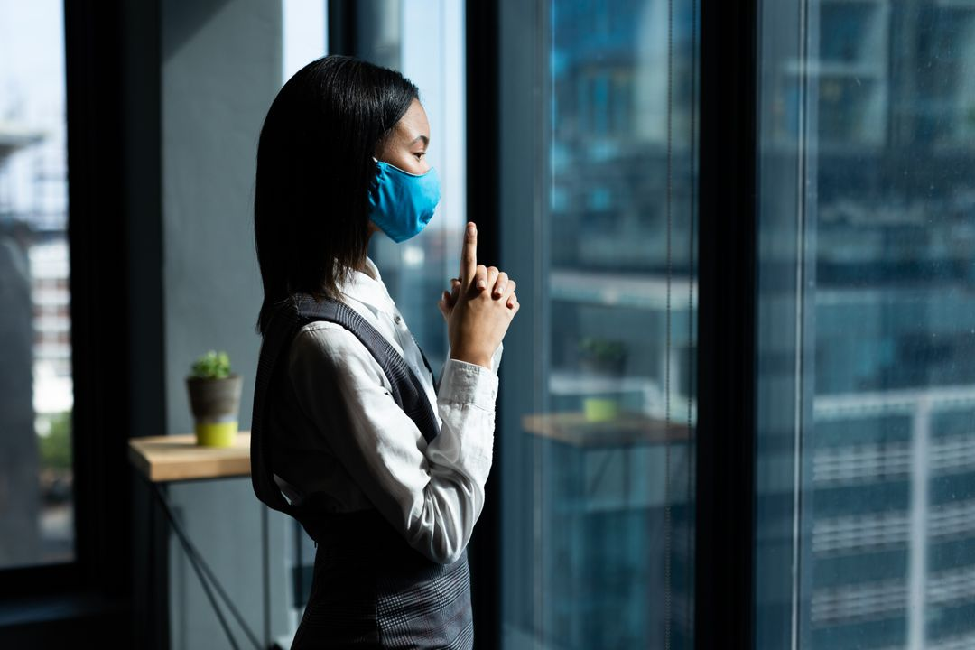 Asian woman wearing face mask standing and looking through window. Health and hygiene in creative office during coronavirus covid 19 pandemic. Free Stock Images from PikWizard