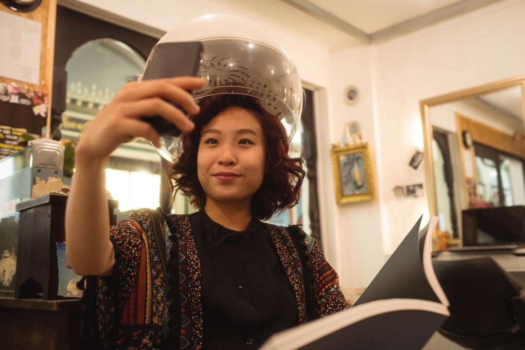 Stylish woman taking a selfie while sitting under a hairdryer at hair salon