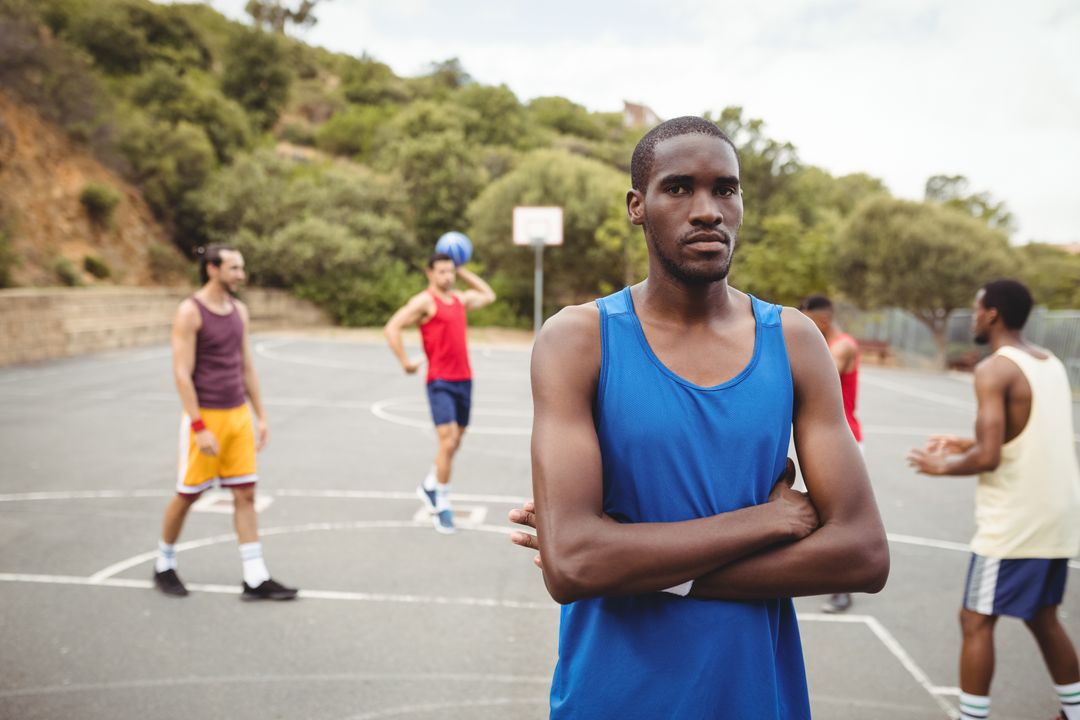 Portrait of male basketball player standing with his crossed in the court Free Stock Images from PikWizard