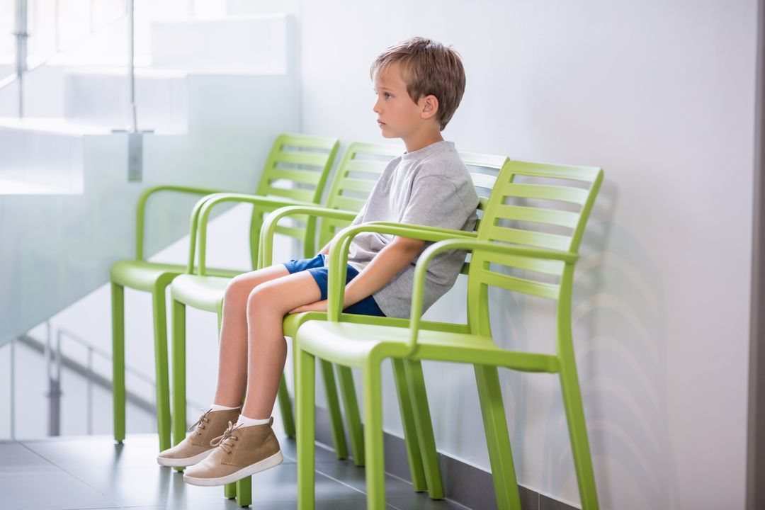 Upset boy sitting on chair in corridor at hospital Free Stock Images from PikWizard