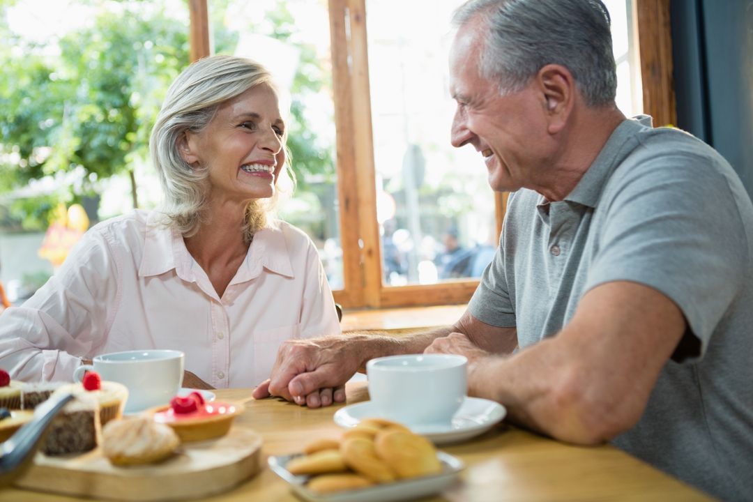 Senior couple interacting with each other in café