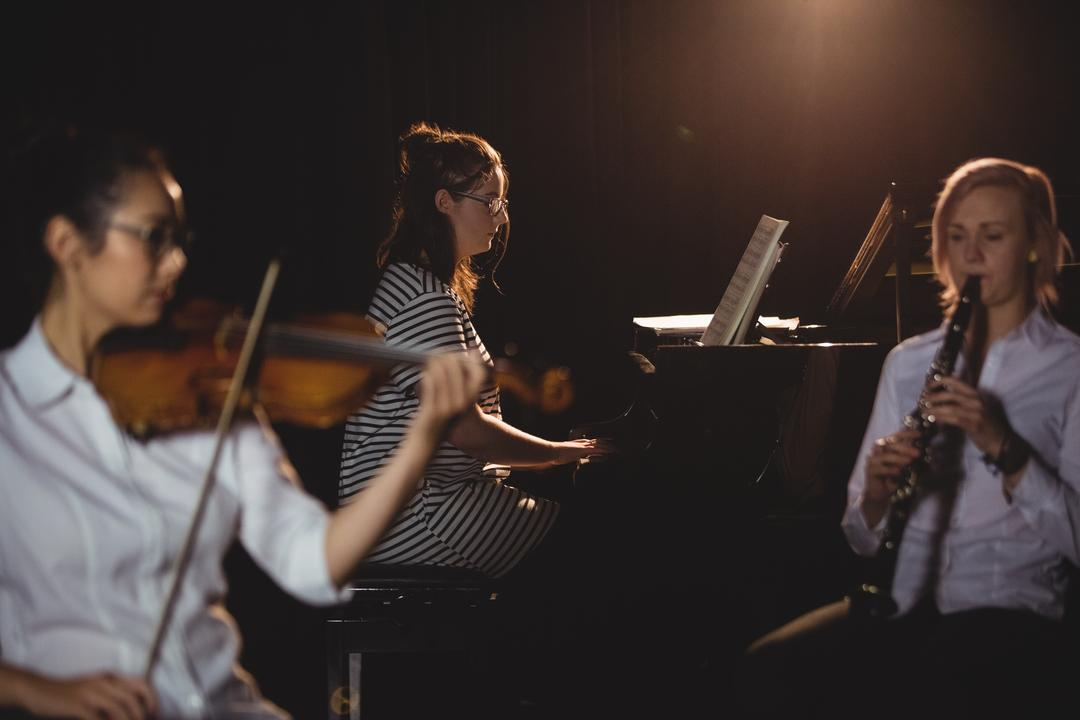 Three female students playing piano, clarinet and violin in a studio