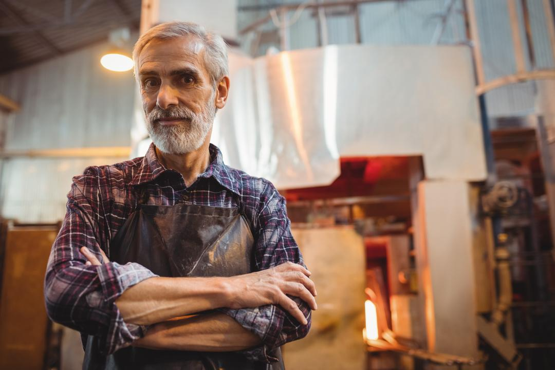 Portrait of glassblower standing with arms crossed at glassblowing factory