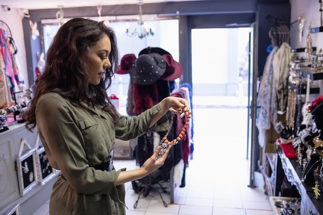 Woman selecting necklace in jewelry section of boutique