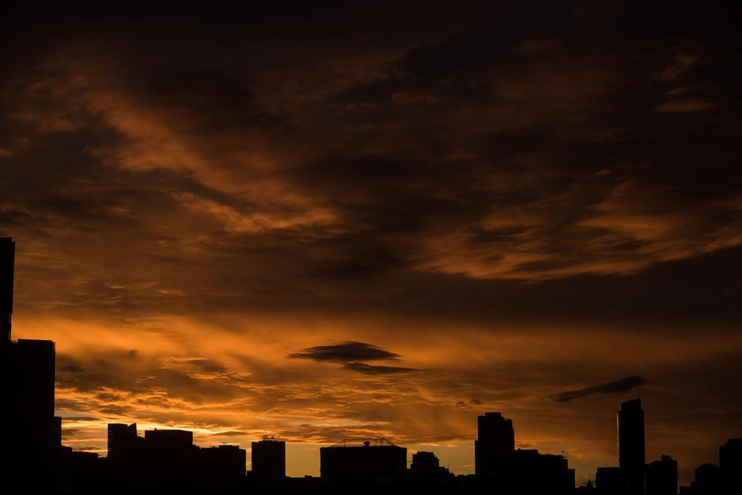 View of silhouette cityscape during sunset