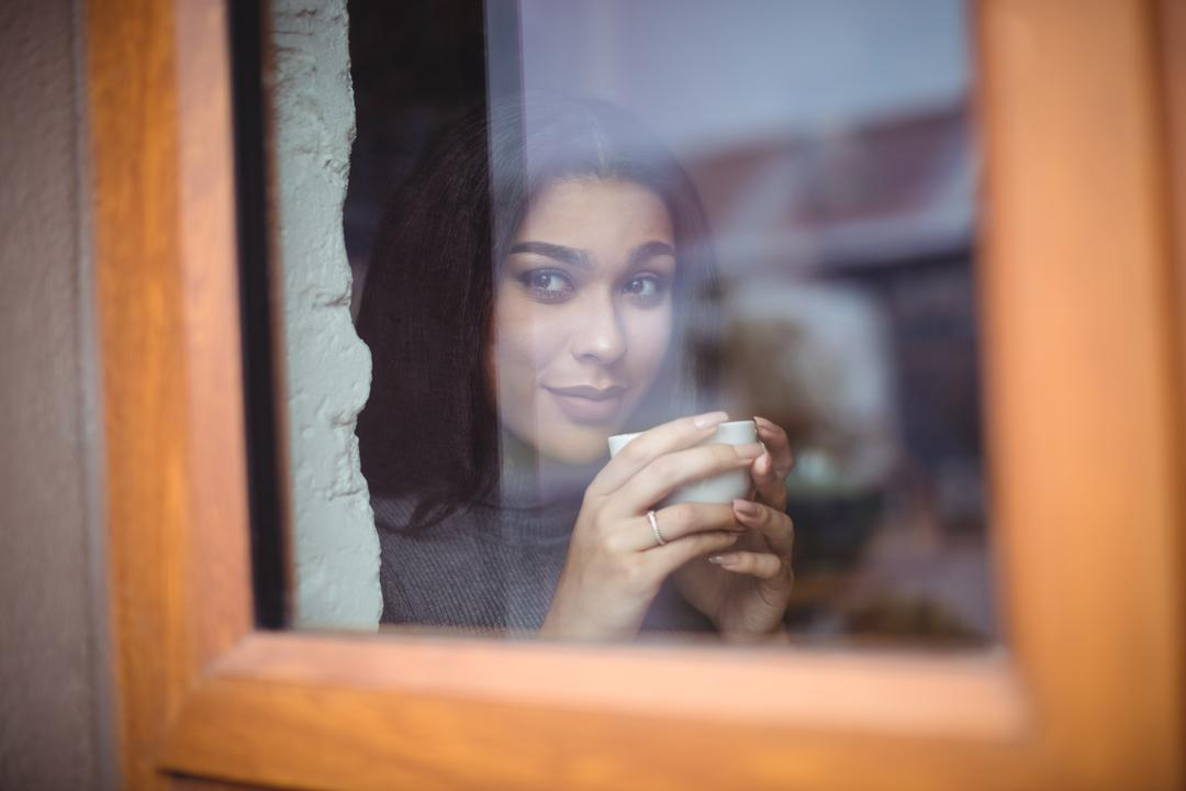 Thoughtful woman having a cup of coffee in café