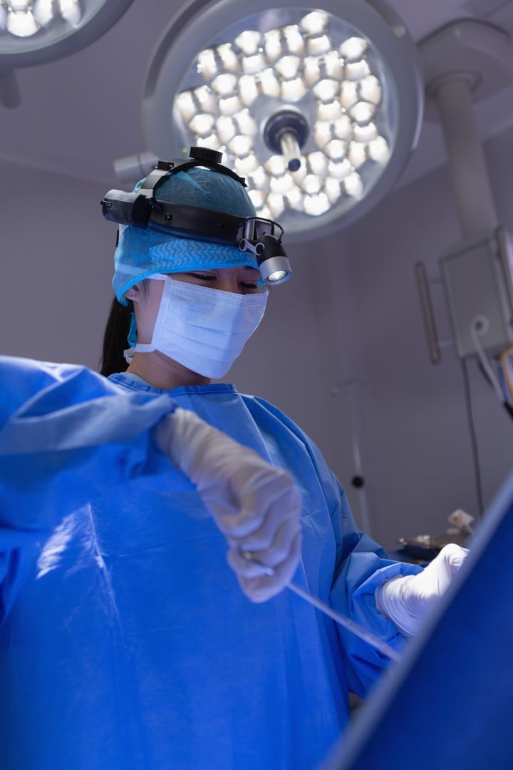 Low angle view of female surgeon performing operation in operation room at hospital