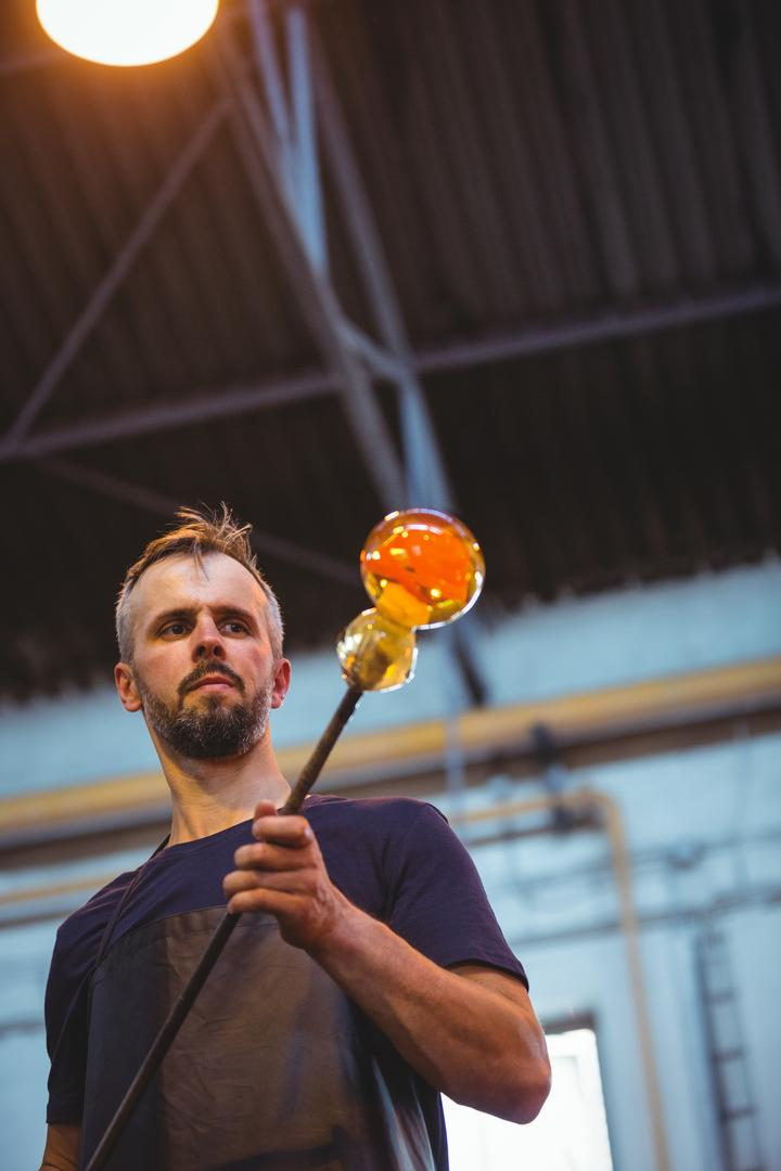 Glassblower shaping a molten glass at glassblowing factory Free Stock Images from PikWizard