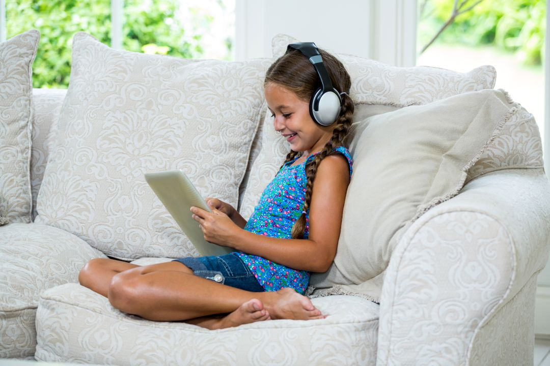 Cheerful girl using digital tablet while listening music on sofa at home Free Stock Images from PikWizard