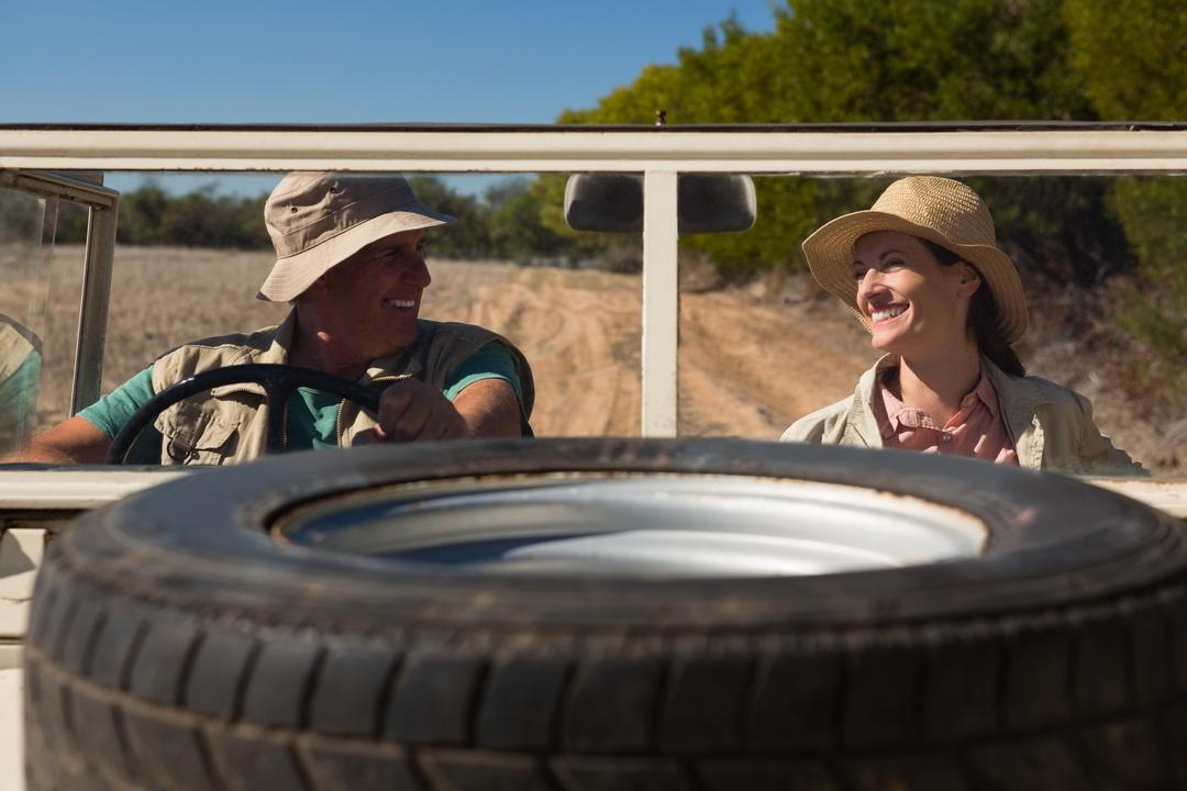 Tire on hood with smiling couple sitting in off road vehicle at landscape