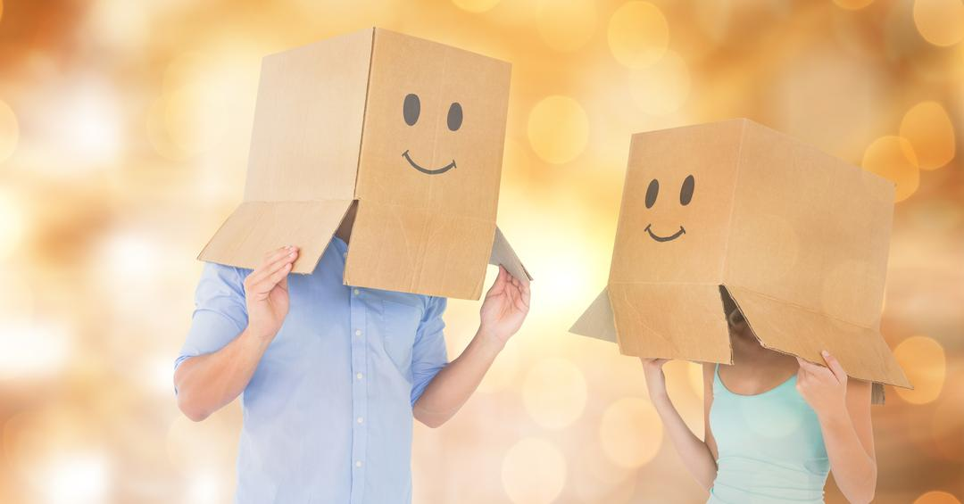 Couple with emojis on cardboard boxes over bokeh