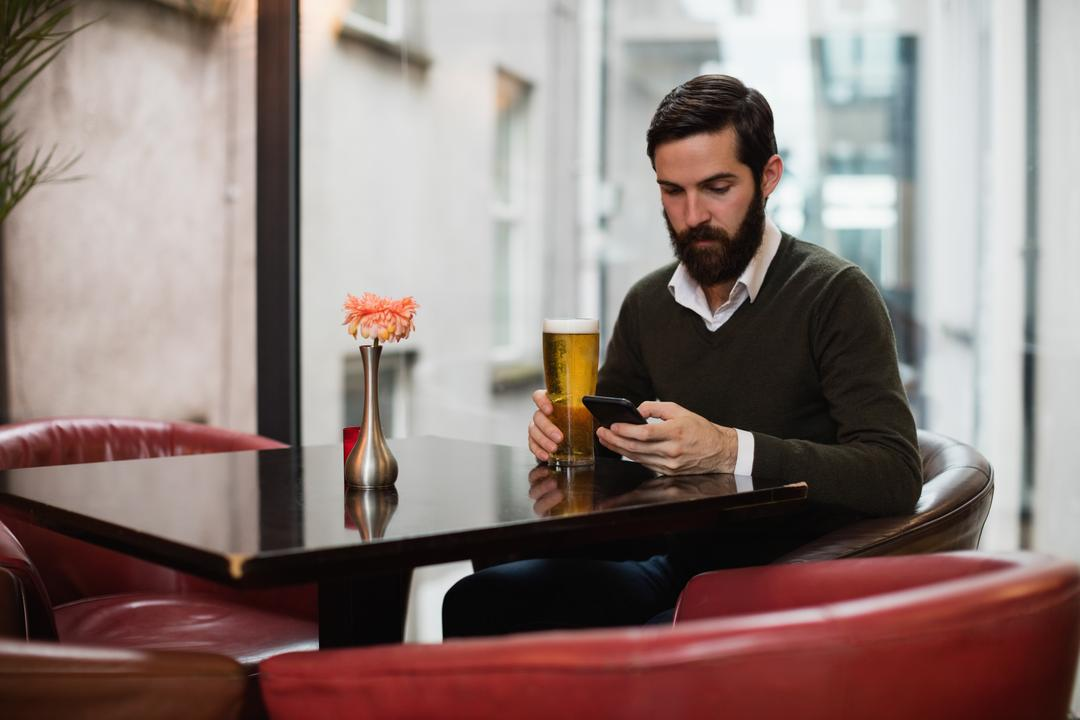 Man using mobile phone while having glass of beer in bar Free Stock Images from PikWizard