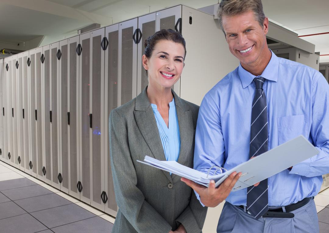 Portrait of business executives standing and holding a file in database server room