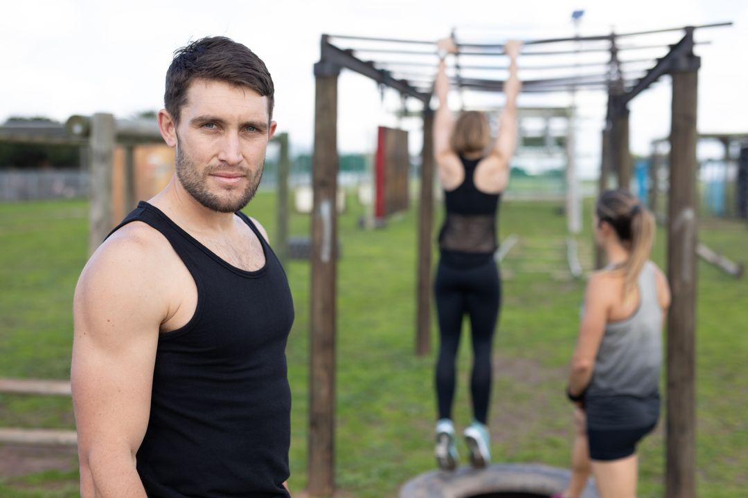Portrait of a fit Caucasian man wearing a black vest looking to camera at an outdoor gym during a bootcamp training session, with two women at the monkey bars in the background Free Stock Images from PikWizard