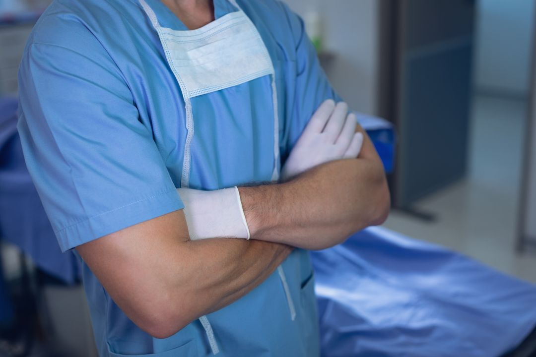 Mid section of male surgeon standing with arms crossed in operating room at hospital