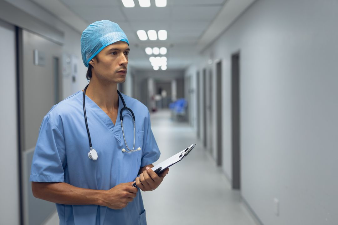 Thoughtful male surgeon holding clipboard in the corridor at hospital Free Stock Images from PikWizard