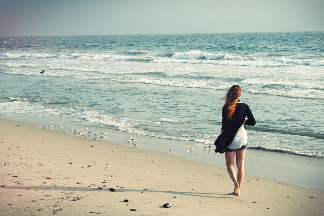 Woman in White and Black Dress on Seashore during Daytime