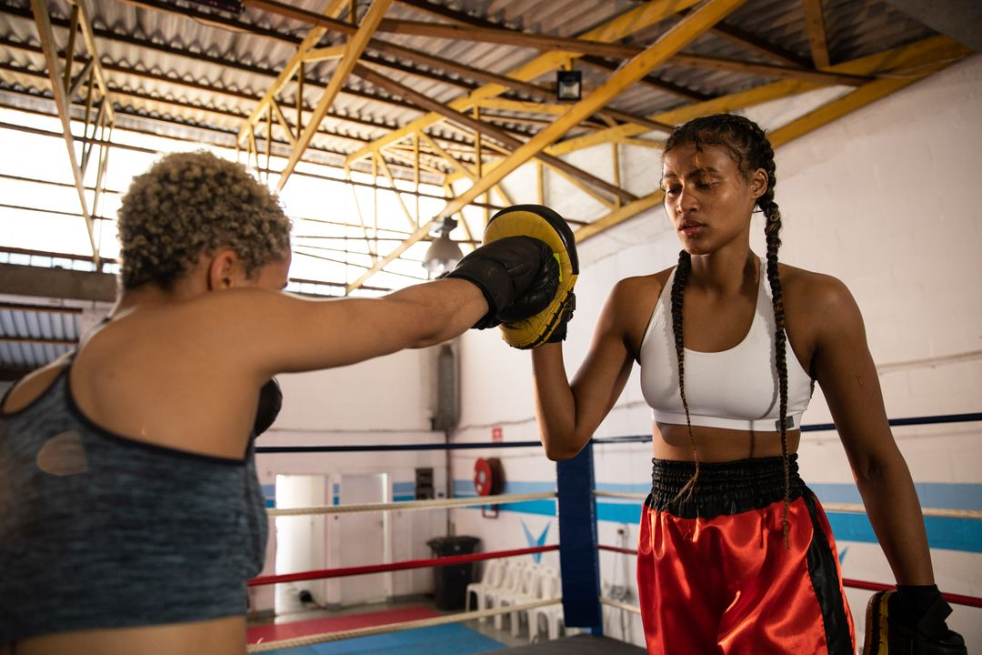 Two mixed race female boxers practicing in a boxing gym wearing sports clothes, one woman punching with boxing gloves on the other holding boxing pad. Strength sports achievement. Free Stock Images from PikWizard