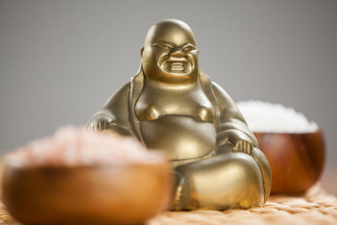 Laughing buddha figurine and sea salt in wooden bowl on mat