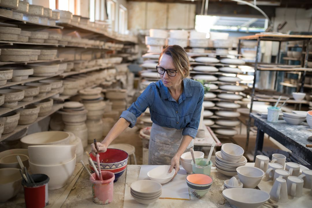 Female potter painting bowl in pottery workshop Free Stock Images from PikWizard