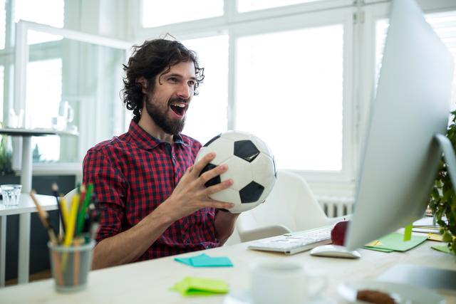 Man with football infront of computer screen in ofefice