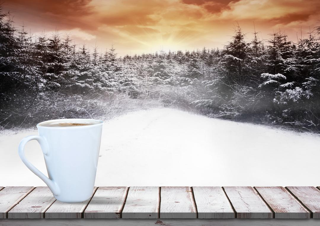Digital composite image of coffee mug kept on wooden plank against snow forest background