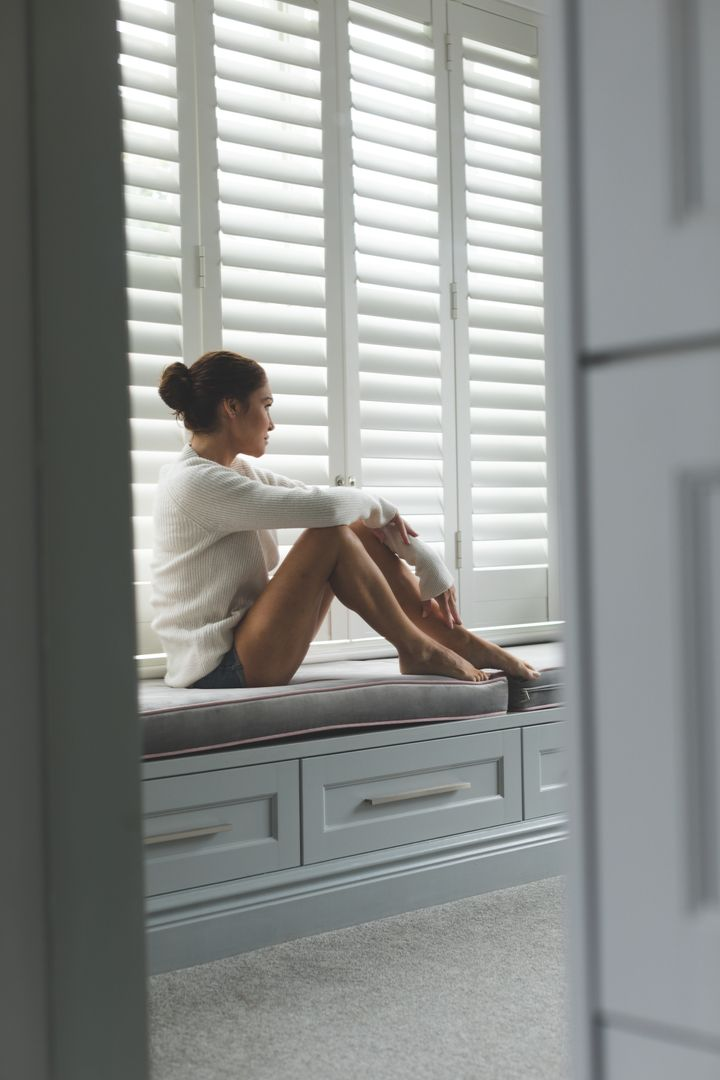 Thoughtful woman sitting on window seat at home