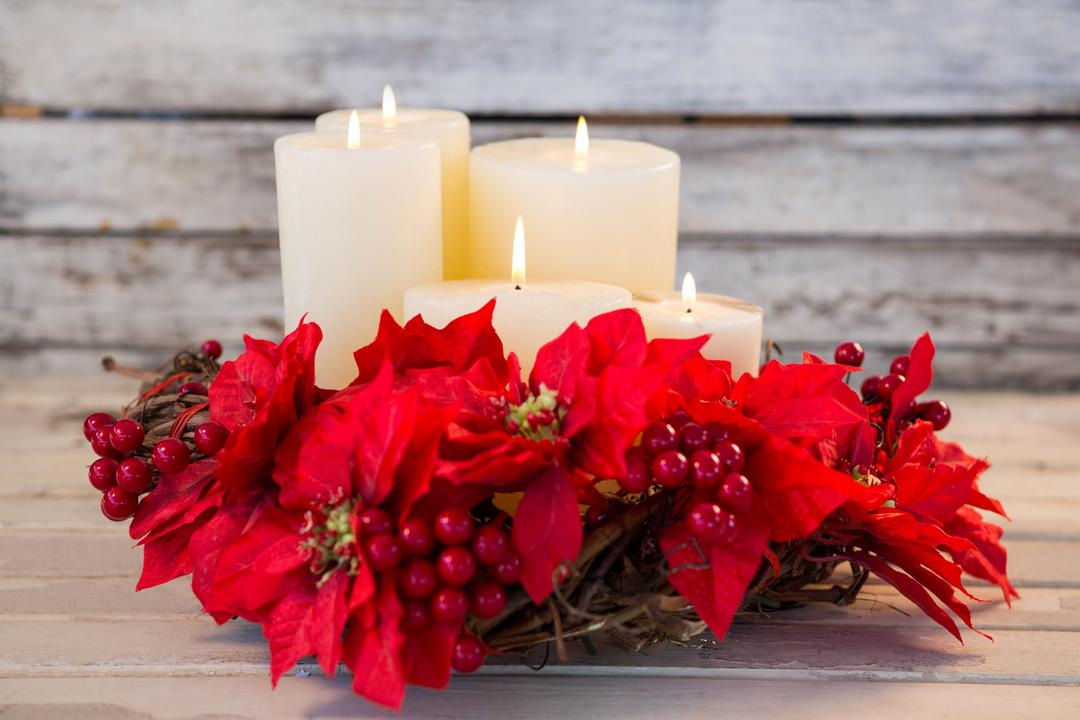 Candles decorated with flowers nest basket on wooden plank during christmas time Free Stock Images from PikWizard