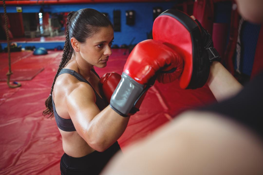 Female boxer practicing with trainer at fitness studio Free Stock Images from PikWizard