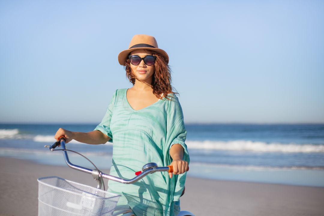 Front view of beautiful mixed race woman with bicycle standing on beach in the sunshine