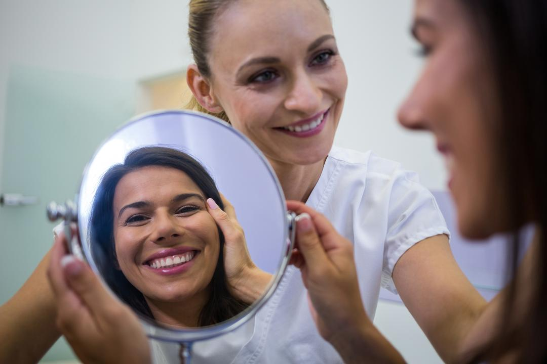 Happy woman checking her skin in the mirror after receiving cosmetic treatment Free Stock Images from PikWizard