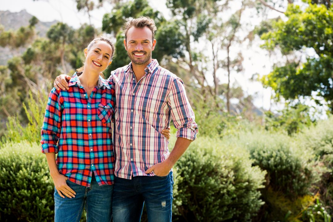 Portrait of smiling couple standing against trees at lawn