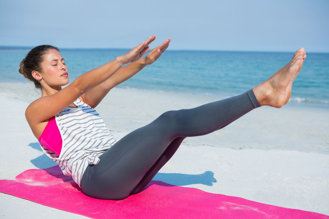 Full length of young woman with eyes closed exercising on mat at beach during sunny day