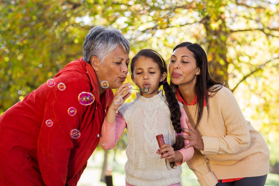 Daughter with mother and grandmother blowing bubbles at park Free Stock Images from PikWizard